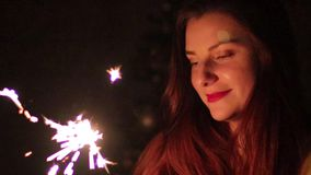 Closeup sparklers portrait of beautiful women celebrating a holiday. Young woman holding sparklers smiling and at home celebrating a holiday stock video