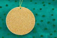 Gold decoration on green. Closeup of a sparkling gold circular decoration on a string flat against a green dotted fabric background Royalty Free Stock Image