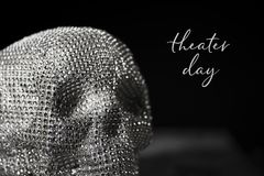 Sparkly skull and text theater day. Closeup of a sparkly skull and the text theater day against a black background Stock Photos