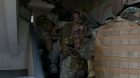 Closeup of special army forces unit entering in a ruined building in search of a high valued terrorist target stock video footage