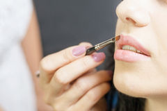 Closeup specialist in beauty salon gets lipstick, lip gloss, make-up. Stock Image