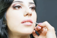 Closeup specialist in beauty salon gets lipstick, lip gloss, make-up. Royalty Free Stock Photography
