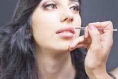 Closeup specialist in beauty salon gets lipstick, lip gloss, make-up. Stock Photos