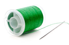 Closeup of a spool of thread and a need. Horizontal extreme closeup of a spool of green thread and a needle Stock Photography
