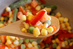Closeup spoon with frozen mixed vegetables Stock Photo