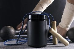Concept of sporty lifestyle and nutrition. Protein can, jump rope and old grey dumbbells royalty free stock photography