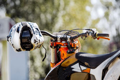 Closeup sports helmet hanging on handlebars. Of a racing motorcycle Royalty Free Stock Photography