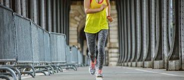 Closeup on sportswoman running on Pont de Bir-Hakeim bridge Stock Photos