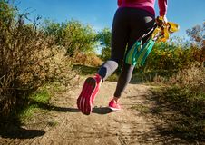 Outdoor resistance training. Closeup of sportswoman with suspension straps walking on autumn road Stock Photo