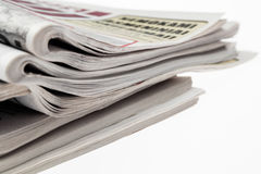 Closeup of stack of newspapers. Assortment of folded newspapers isolated on white. Breaking news, journalism, power of the media, Royalty Free Stock Image