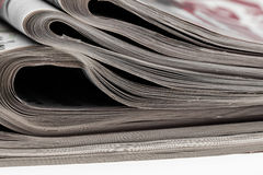 Closeup of stack of newspapers. Assortment of folded newspapers  on white. Breaking news, journalism, power of the media, Royalty Free Stock Image