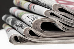 Closeup of stack of newspapers. Assortment of folded newspapers  on white. Breaking news, journalism, power of the media, Royalty Free Stock Photo