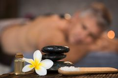 Male spa setting with black hot stones. Closeup of stacked black hot stones on wooden table with oil, rock salt and frangipani flower. Zen stones in spa center Royalty Free Stock Image