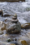 Closeup of stacked rocks in flowing water. Closeup of stacked rocks on the side of a flowing river stock images