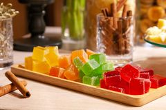Closeup of stacks of small cubes of green, red, yellow, orange marmalade and cinnamon sticks in crystal glass on rectangular stock photos