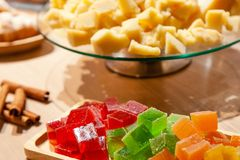 Closeup of stacks of small cubes of green, red, yellow, orange marmalade, glass round plate with hard parmesan cheese and cinnamon stock image