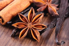 Closeup of star anise, fragrant vanilla and cinnamon on wooden surface plank Stock Image