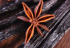 Closeup of star anise and fragrant vanilla on wooden surface plank Royalty Free Stock Images