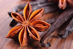 Closeup of star anise and fragrant vanilla on wooden surface plank Stock Images