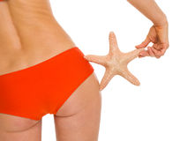 Closeup on starfish in hand of woman in swimsuit Stock Photo