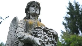 Closeup statue of angel holding wreath at cemetery Royalty Free Stock Photography