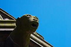 Closeup of statue of gargoyle against a bright blue background, Aberdeen, Scotland royalty free stock photo