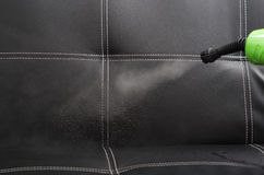 Closeup steam exiting nozzle of vapor cleaning machine, rinsing black leather couch Royalty Free Stock Images