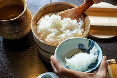 Closeup steamed japanese white rice in traditional wooden bowl with serving hands and wooden table background. Japan Stock Image