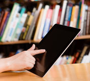 Closeup stedent using tablet computer in library Royalty Free Stock Images