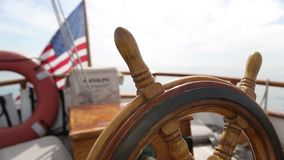 Closeup of a steering wheel and deck of a wooden antique Sail boat navigating in the ocean sunny day showing the wooden parts and. Sail boat navigating in the stock video footage