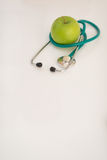 Closeup on stethoscope and apple on table Stock Photography
