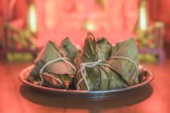 Closeup Sticky rice dumpling or Zongzi on stainless steel tray in front of Chinese spirit`s house during Dragon Boat Festival. Pay respect to ancestor royalty free stock photography