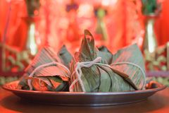 Closeup Sticky rice dumpling or Zongzi on stainless steel tray in front of Chinese spirit`s house during Dragon Boat Festival. Pay respect to ancestor stock photos