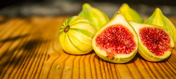 Closeup still life of group of whole panachee variegated striped figs on brown wooden cutting board with one fig sliced in half in Stock Photos