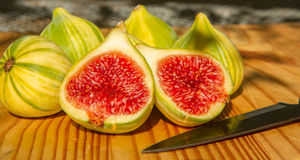 Closeup still life of group of whole panachee variegated striped figs on brown wooden cutting board with one fig sliced in half in Royalty Free Stock Photos