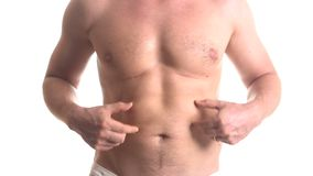Man checking his stomach. Closeup stomach of man in shorts checking his stomach isolated over white background stock video footage