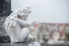 Stoned angel sitting on tomb in a cemetery. Closeup of stoned angel sitting on tomb in a cemetery Royalty Free Stock Photo