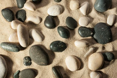 Closeup of stones sticking out of the sand in the sunlight Royalty Free Stock Photography