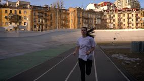 Closeup straight view portrait of young attractive fit caucasian female jogging outdoors on the stadium in the urban. City stock video