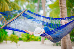 Closeup straw beach hat near relaxing young woman in hammock Royalty Free Stock Image