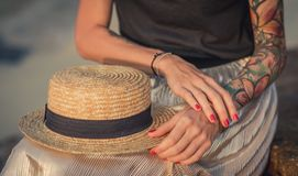 Closeup of a straw hat rests on his knees. Female hand with tattoos correct bracelets. The modern woman royalty free stock images