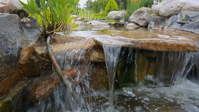 Closeup of stream flowing in the decorative garden stock video footage