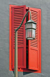 Closeup of streetlamp and red shuttered window Royalty Free Stock Photo