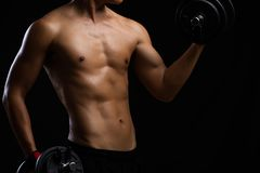 Closeup of a strength fitness body with dumbbell and sweat. Fit young man with beautiful torso. Beginner Bodybuilder and muscular. Body concept royalty free stock photography