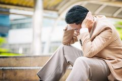 Stressed Asian businessman to touch his head feeling Stock Images