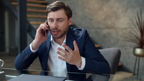 Stressed businessman talking on phone emotionally. Focused man calling phone.