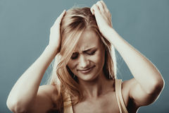Closeup stressed girl holds head with hands Stock Photography