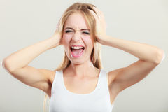Closeup stressed woman covers ears with hands Royalty Free Stock Photography