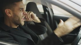 Closeup of Stressed businessman swearing and talking phone while sitting inside car outdoors Stock Images