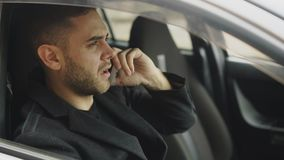 Closeup of Stressed businessman swearing and talking phone while sitting inside car outdoors Royalty Free Stock Image